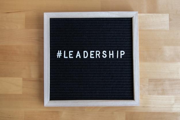 나무 테이블에 리더십 인용문이 있는 칠판의 상위 뷰 샷