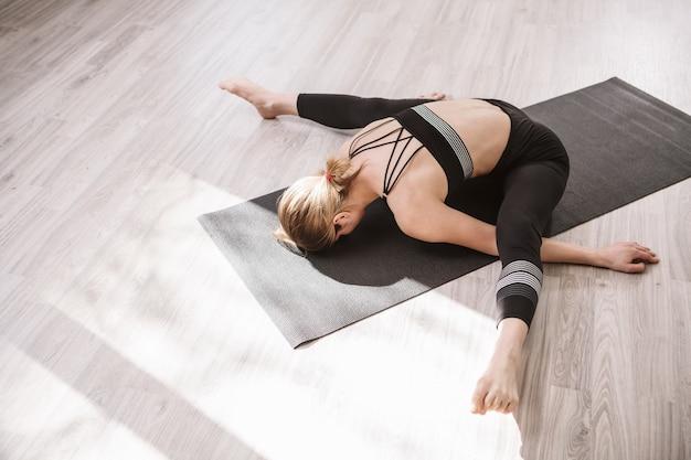 体育館の床に伸びる柔軟な女性体操選手のトップ ビュー ショット