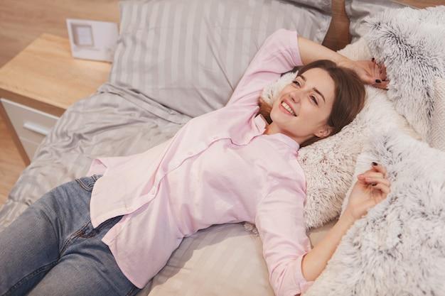 Вид сверху счастливой красивой женщины, лежащей на кровати, радостно улыбаясь