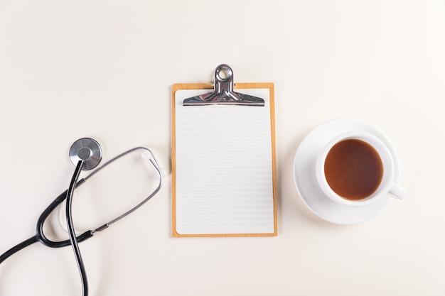 Снимок блокнота, медицинского стетоскопа и чашки горячего чая, вид сверху