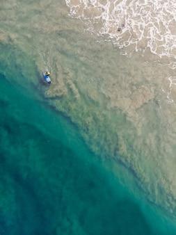 Varkala 해변에서 수영하는 서핑 보드를 가진 사람의 상위 뷰 샷