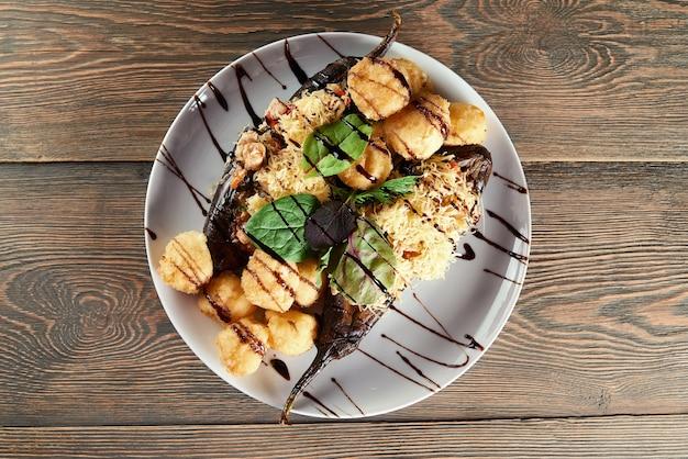 Снимок вида сверху тарелки, полной жареных сырных шариков, подаваемых с баклажанами и соусом из базилика и бальзамического уксуса, ресторан, кафе, кулинария, кухня, деликатес, аппетит, аппетит.