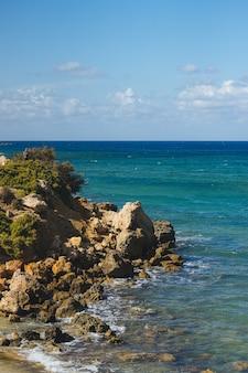 낮 동안 바위로 가득한 해변의 상위 뷰 샷