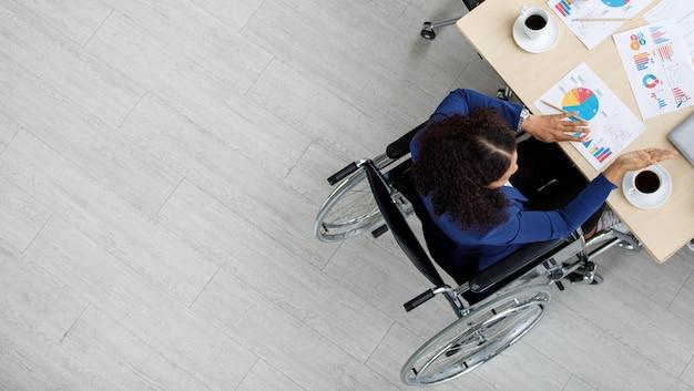 휠체어에 앉아 책상에 앉아 다른 직원들과 회의를 하는 공식적인 업무복을 입은 식별할 수 없는 아시아 여성 장애 여성 사업가의 상위 뷰 샷.
