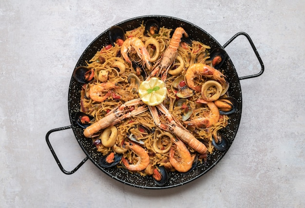 Вид сверху вкусной паэльи с морепродуктами и луковыми кольцами