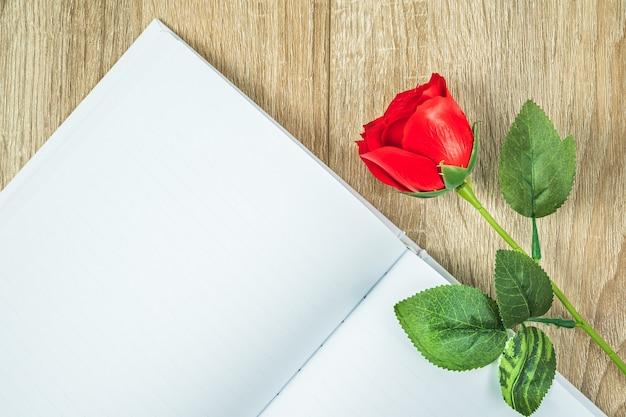 空の空白のノートブック日記と木製のテーブル、バレンタインの概念の赤いバラの平面図のショット