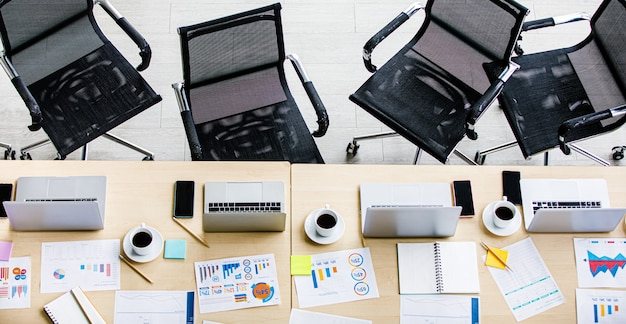 空のオフィスルームのワークスペースの上面図ラップトップノートブックコンピューターグラフチャート図レポート書類文書ホワイトホットブラックコーヒーカップ鉛筆スマートフォンポストそれと椅子。