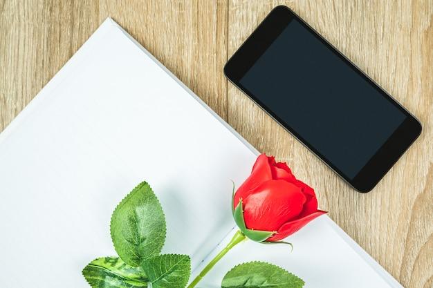 空白のノートブック日記と木製のテーブル、バレンタインコンセプトのスマートフォンの赤いバラの上面図