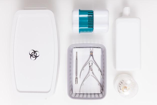Вид сверху стерилизационной коробки и флакона с жидким дезинфицирующим средством возле маникюрных инструментов