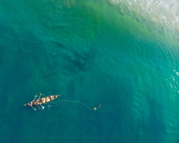 Top view shot of people in a boat fishing in varkala beach