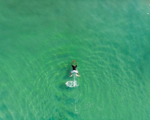 Inquadratura dall'alto di una persona che nuota nella spiaggia di varkala