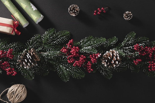 Top view shot of pine branches with cone and gift on a black background