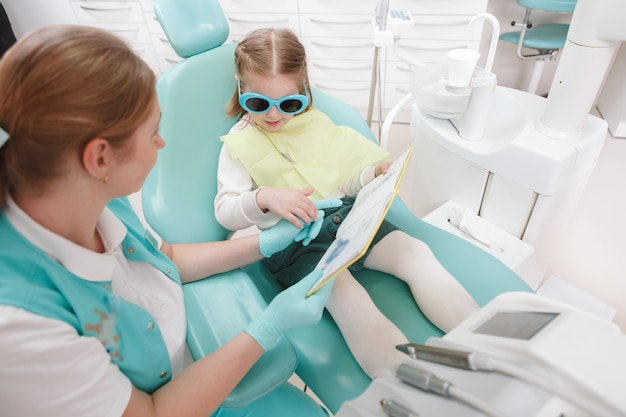 Top view shot of a professional dentist reading a book with her little patient after dental exam
