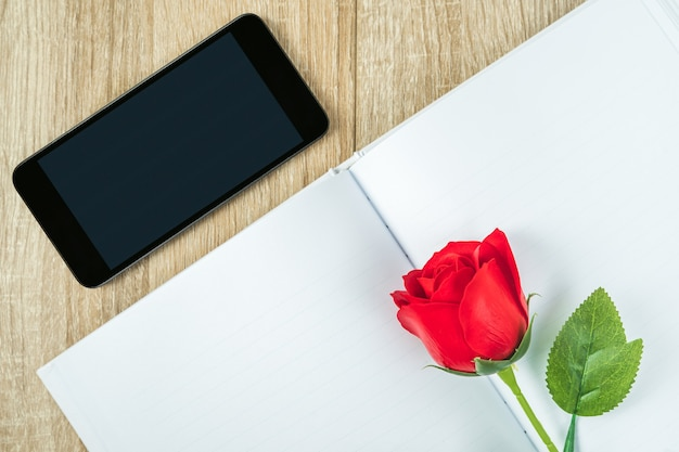 Top view shot of red roses on blank notebook diary and  smartphone on wood table,valentine concept