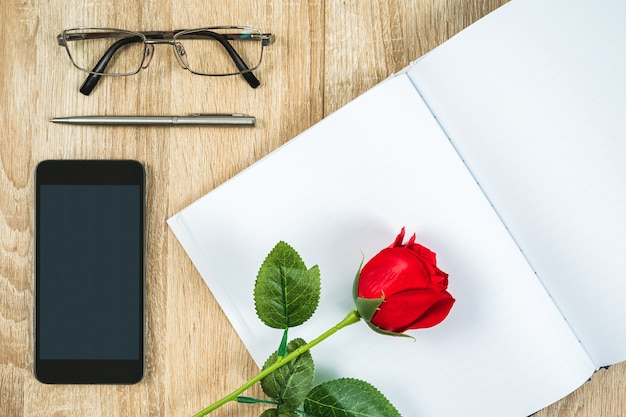 Top view shot of red roses empty blank notebook diary and eye glasses with smartphone on wood table,valentine concept