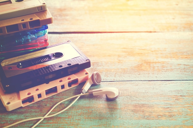 Top view (above) shot of retro tape cassette with earphone on wood table - vintage color effect styles.