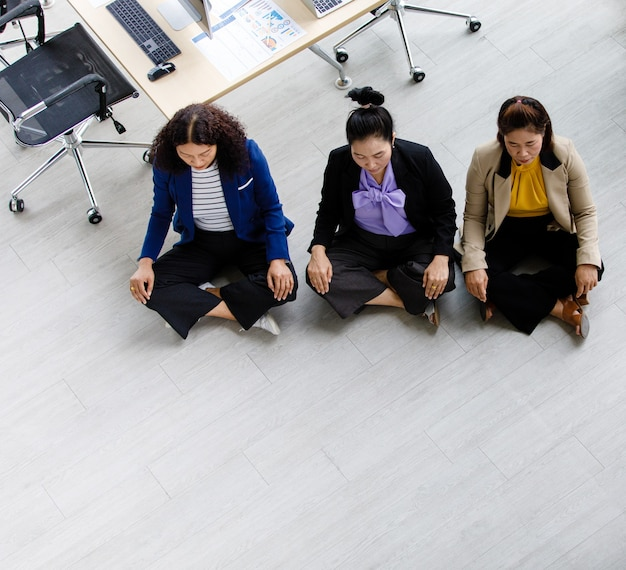 Top view shot of three asian middle aged female businesswoman officer staffs in formal suit sitting squat quiet on floor close eyes meditating together at office working station table in company.