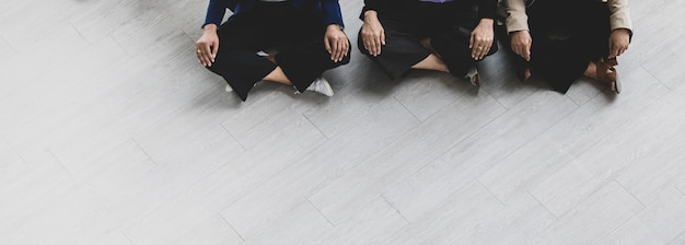 Top view shot of unidentified unrecognizable calm peaceful relaxation female businesswoman officer worker staffs in formal suit sitting squat resting quiet on floor meditating together side by side.