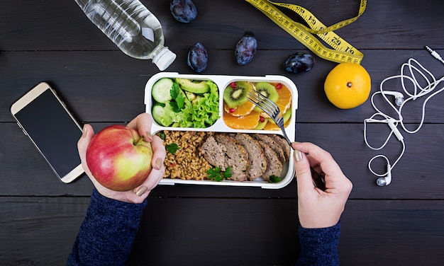 Top view showing hands eating healthy lunch with bulgur, meat and fresh vegetables and fruit