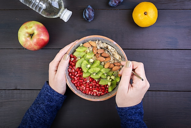 Top view showing hands eating healthy oatmeal with kiwi and almond on a wooden table.