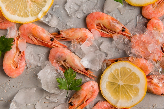 Top view shrimp on ice with slices of lemon