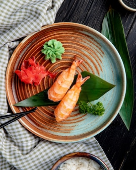 Top view of shrimp nigiri sushi on bamboo leaf served with pickled ginger slices and wasabi on a plate