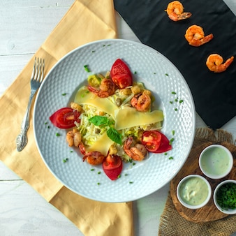 Top view of shrimp salad with cheese and tomatoes on a white plate