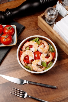 Top view of shrimp salad with green peppers and tomatoes in a bowl