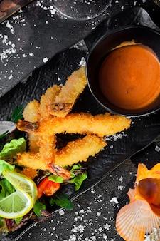 Вид сверху креветки в кляре с соусом и салатом из свежих овощей и ракушками в лотке
