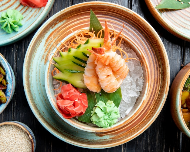 Top view of shrimps with sliced cucumbers and ginger on bamboo leaf on ice cubes in a plate on the table