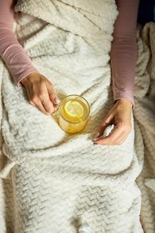 Вид сверху больная женщина, держащая кружку теплого чая из облепихи и сидящая под одеялом дома, больная дама, природные средства от простуды, концепция естественной медицины.