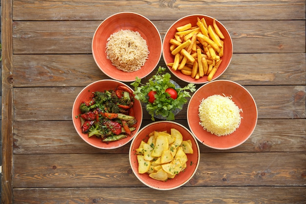 Top view of side dish bowls with fried potatoes, rice and boiled vegetables