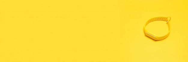 黄色の背景に平面図シリコーンフィットネストラッカーブレスレットns copyspace。ダイエット、栄養、スポーツコンセプト、フラットレイアウト