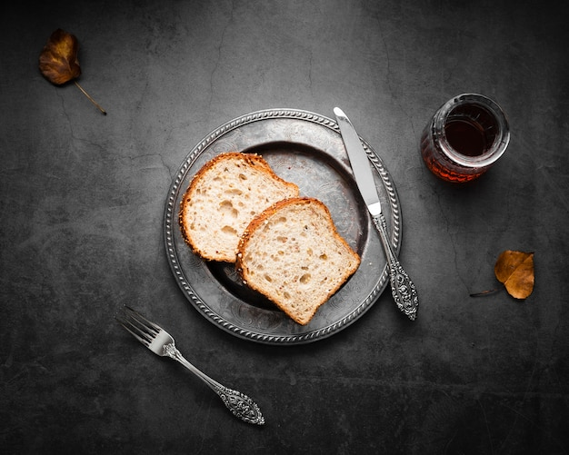 Top view silver cutlery set up with bread and tea