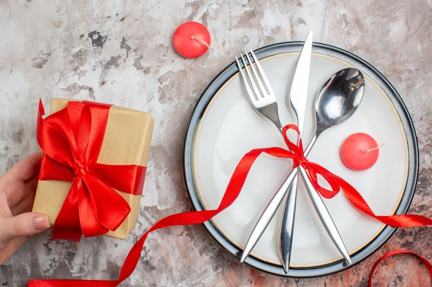Top view silver cutlery spoon fork and knife with red bow and presents on a light surface