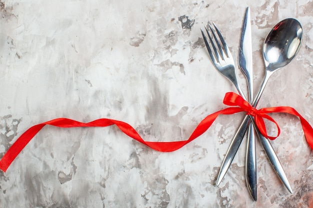 Top view silver cutlery with red bow on light surface