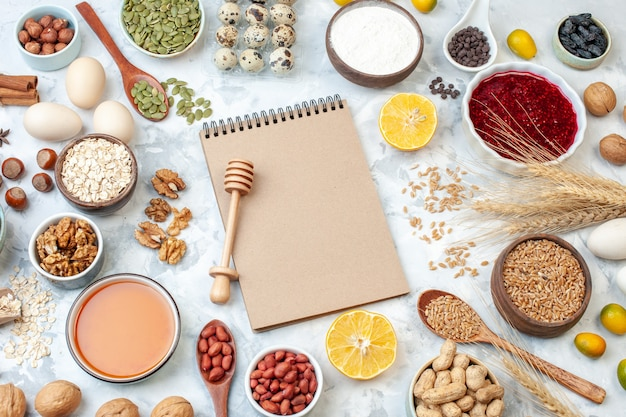 上面図シンプルなメモ帳と卵粉ゼリーさまざまなナッツと種の白いナッツ色のケーキ甘いパイの写真砂糖生地の果実