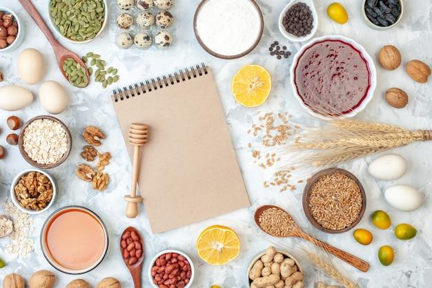上面図シンプルなメモ帳、卵粉ゼリー、さまざまなナッツと種、白いナッツの色のケーキ甘いパイの写真生地の果実