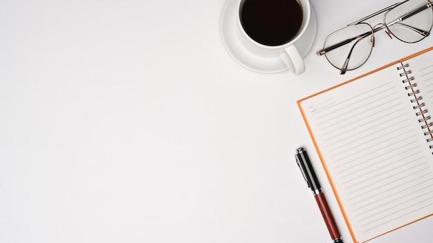 白い机の上にノートブック、コーヒーカップ、グラスを備えた平面図のシンプルなワークスペース。