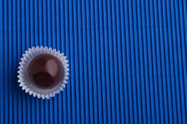 Вид сверху одной коричневой шоколадной конфеты и копией пространства