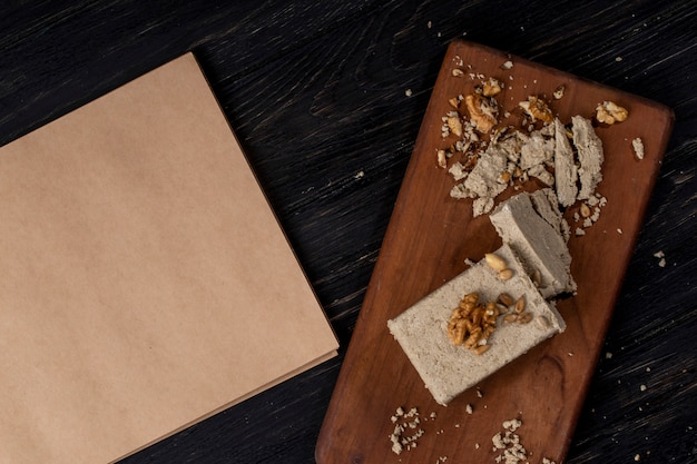 Top view of sketchbook and halva with sunflower seeds and walnuts on a wooden board