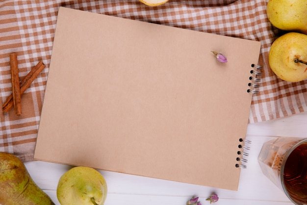 Top view of sketchbook made of craft paper with fresh ripe pears on plaid tablecloth