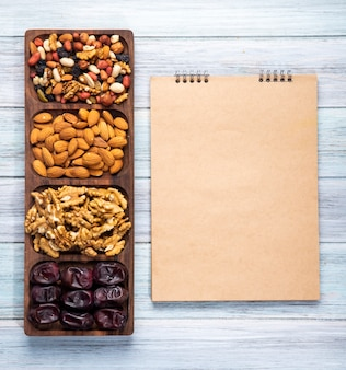 Top view of sketchbook and nuts mix with walnuts almond and sweet dried date fruits on wooden