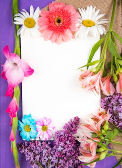 Top view of a sketchbook and pink and purple color flowers gerbera lilac alstroemeria and daisy flowers on sackcloth on purple wooden background