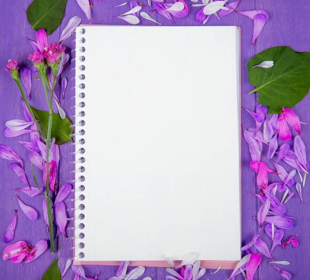 Top view of a sketchbook and purple flower petals scattered around on purple wooden background
