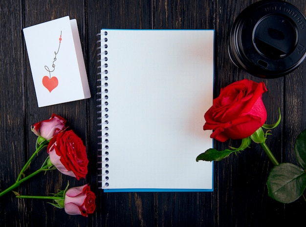 Top view of a sketchbook and red color roses with a postcard and paper cup of coffee on dark wooden background