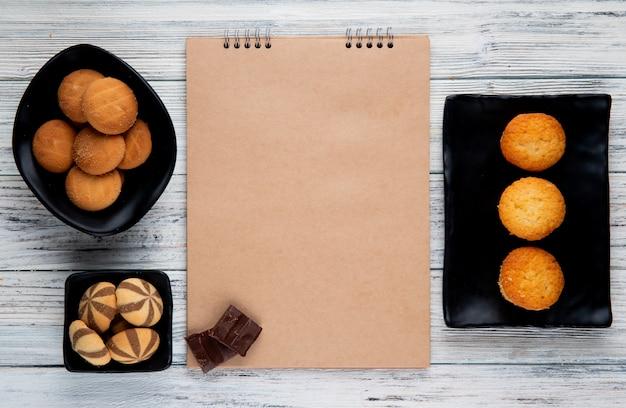 Vista superiore dello sketchbook e vari tipi di biscotti dolci su vassoi neri su fondo di legno