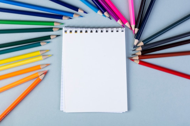 Top view of a sketchbook with colored pencils arranged around on white