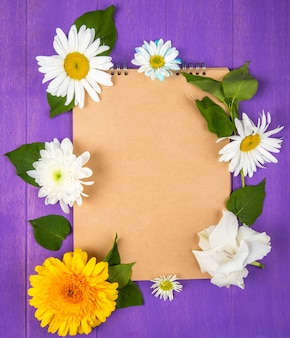 Top view of a sketchbook with daisy and gerbera flowers on purple wooden background