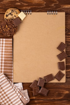 Top view of sketchbook with dark chocolate pieces and oatmeal cookies on wooden background